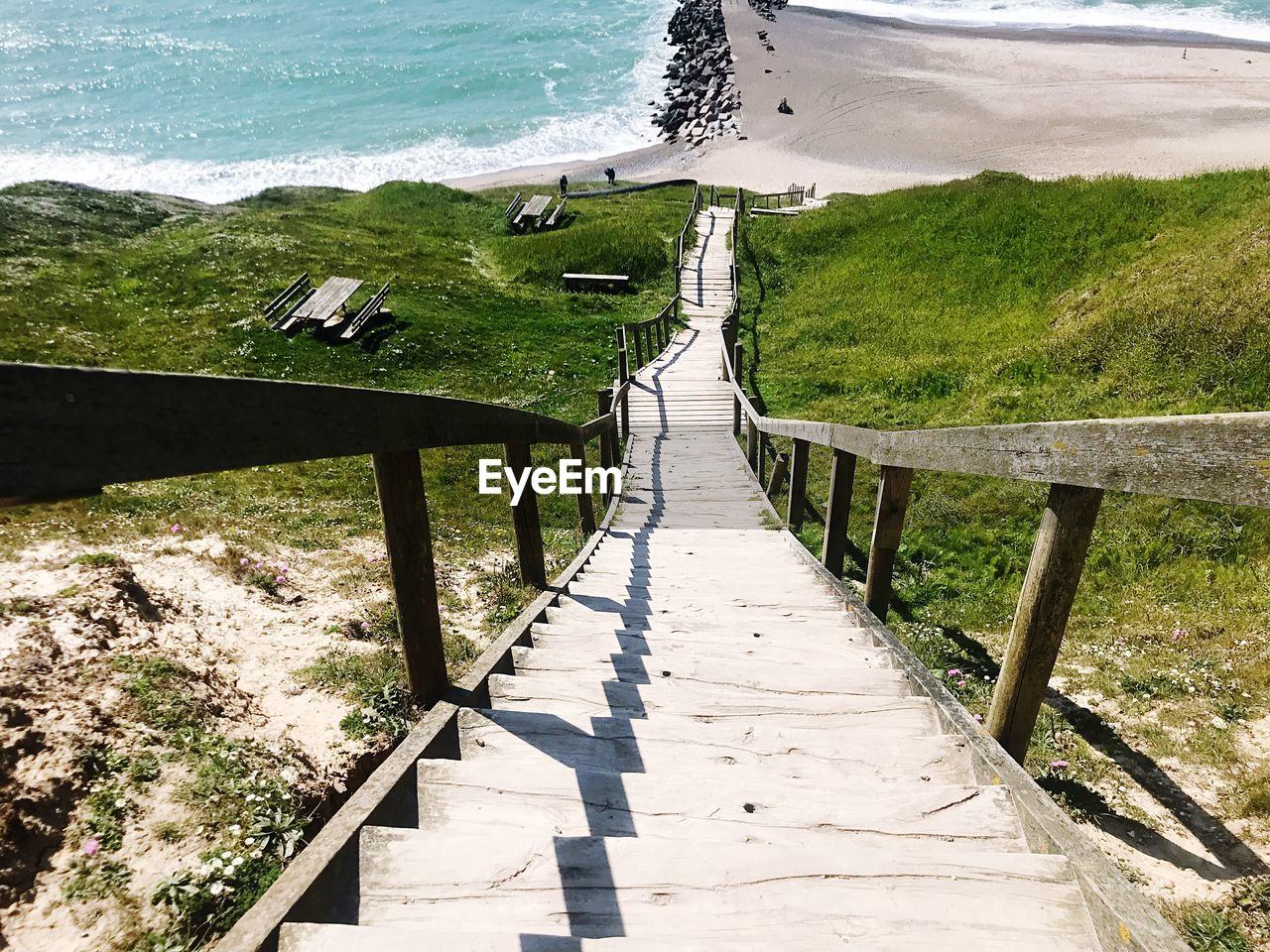 water, sunlight, nature, day, plant, shadow, land, no people, high angle view, wood - material, architecture, beach, green color, beauty in nature, railing, outdoors, footpath, grass, tranquility