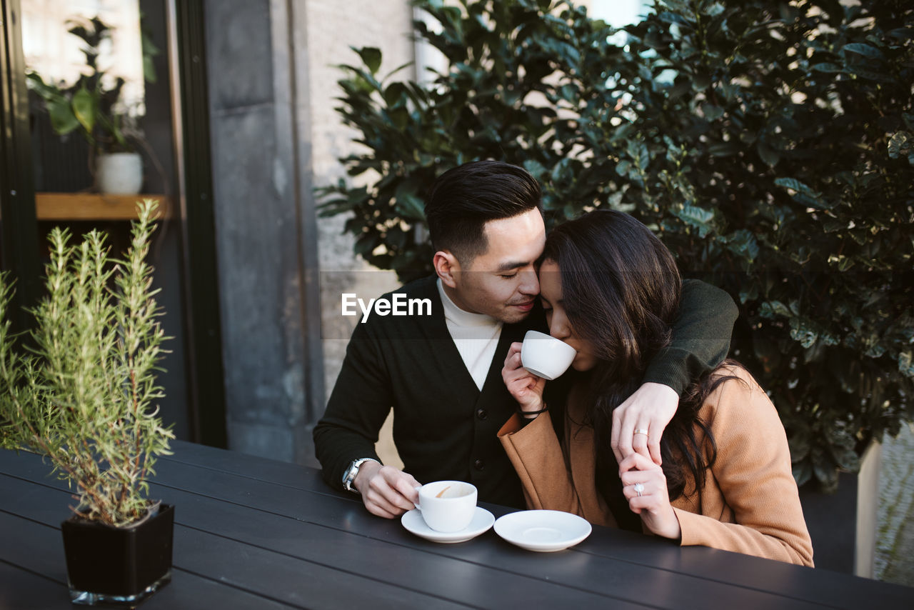 YOUNG COUPLE AND COFFEE AT TABLE