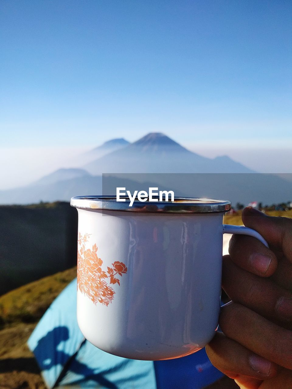 MIDSECTION OF PERSON HOLDING DRINK AGAINST MOUNTAINS