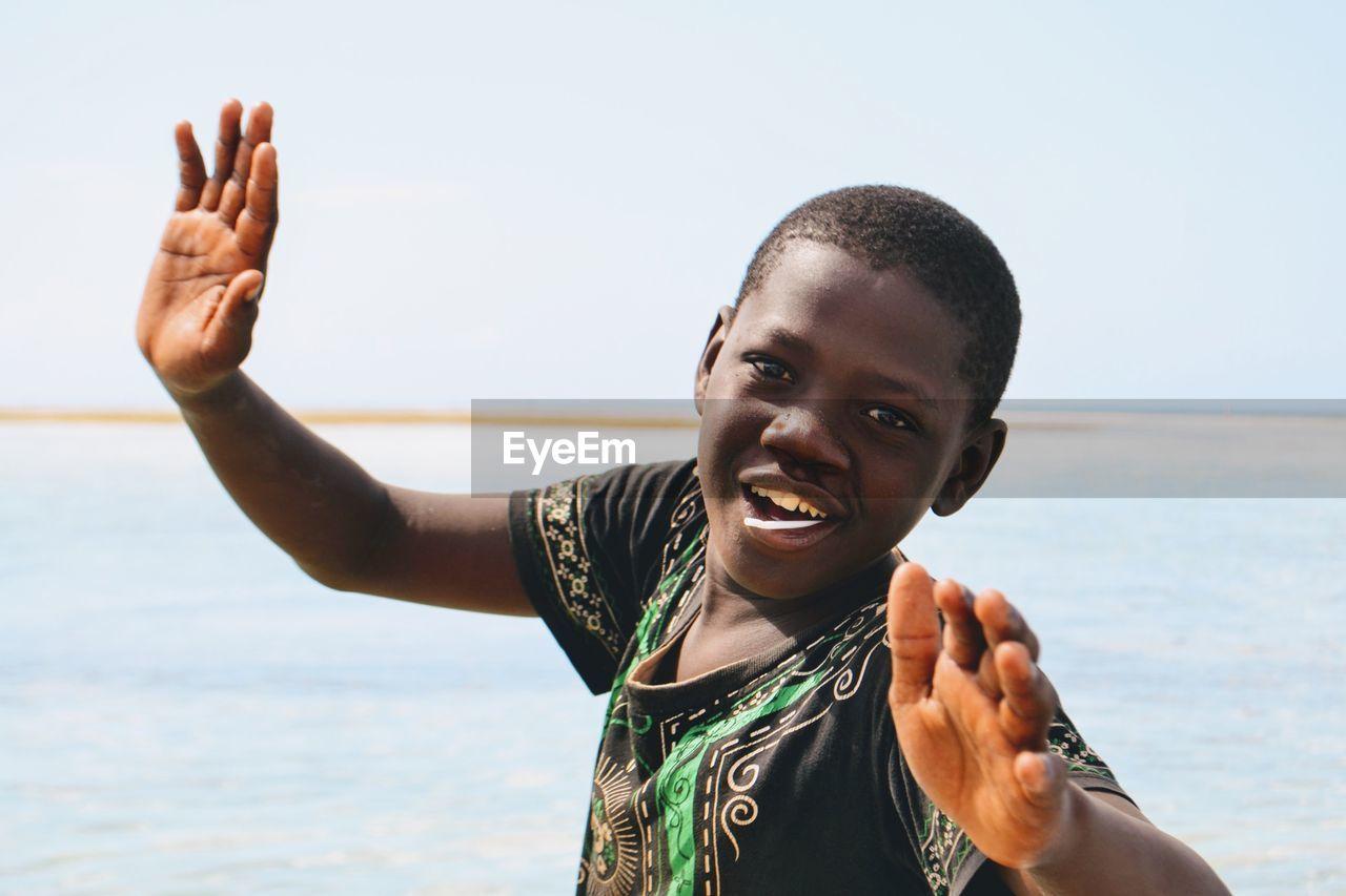 Portrait Of Smiling Cheerful Boy Gesturing Against Sky