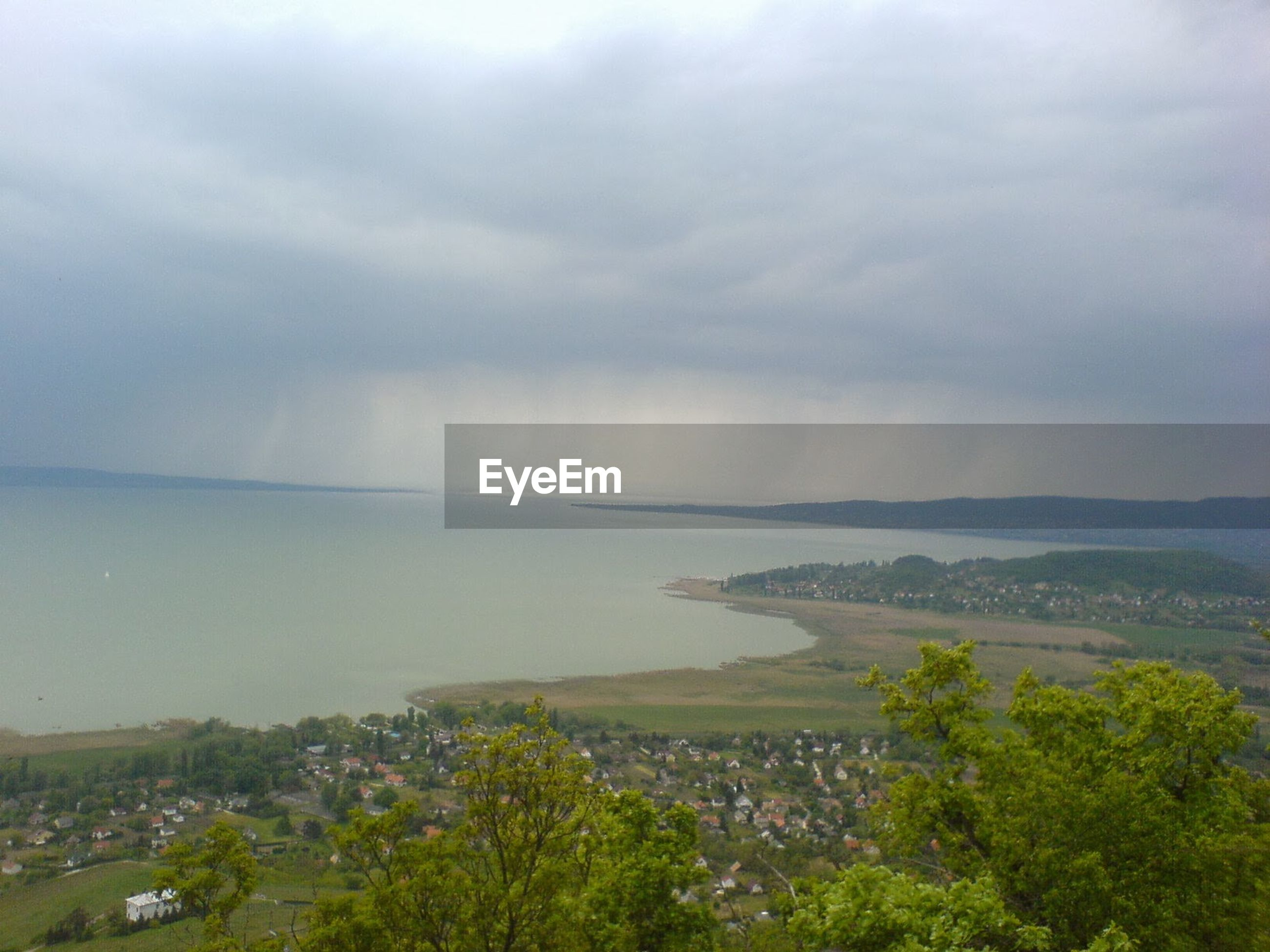 Scenic view of lake and field against cloudy sky