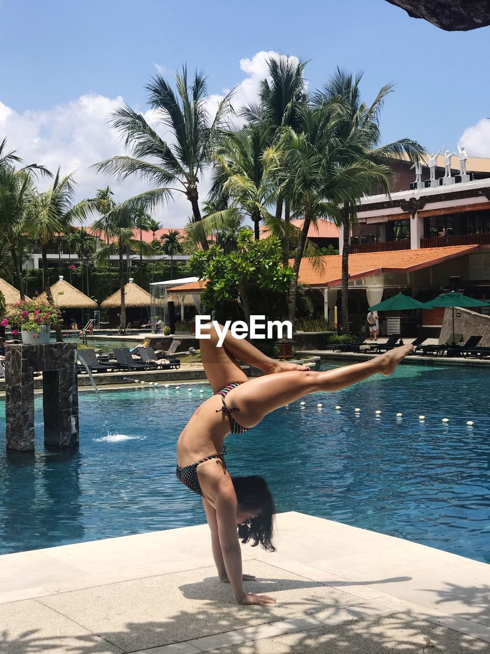 water, tree, swimming pool, palm tree, tropical climate, pool, real people, nature, leisure activity, plant, full length, shirtless, people, lifestyles, young adult, swimwear, sunlight, sky, outdoors