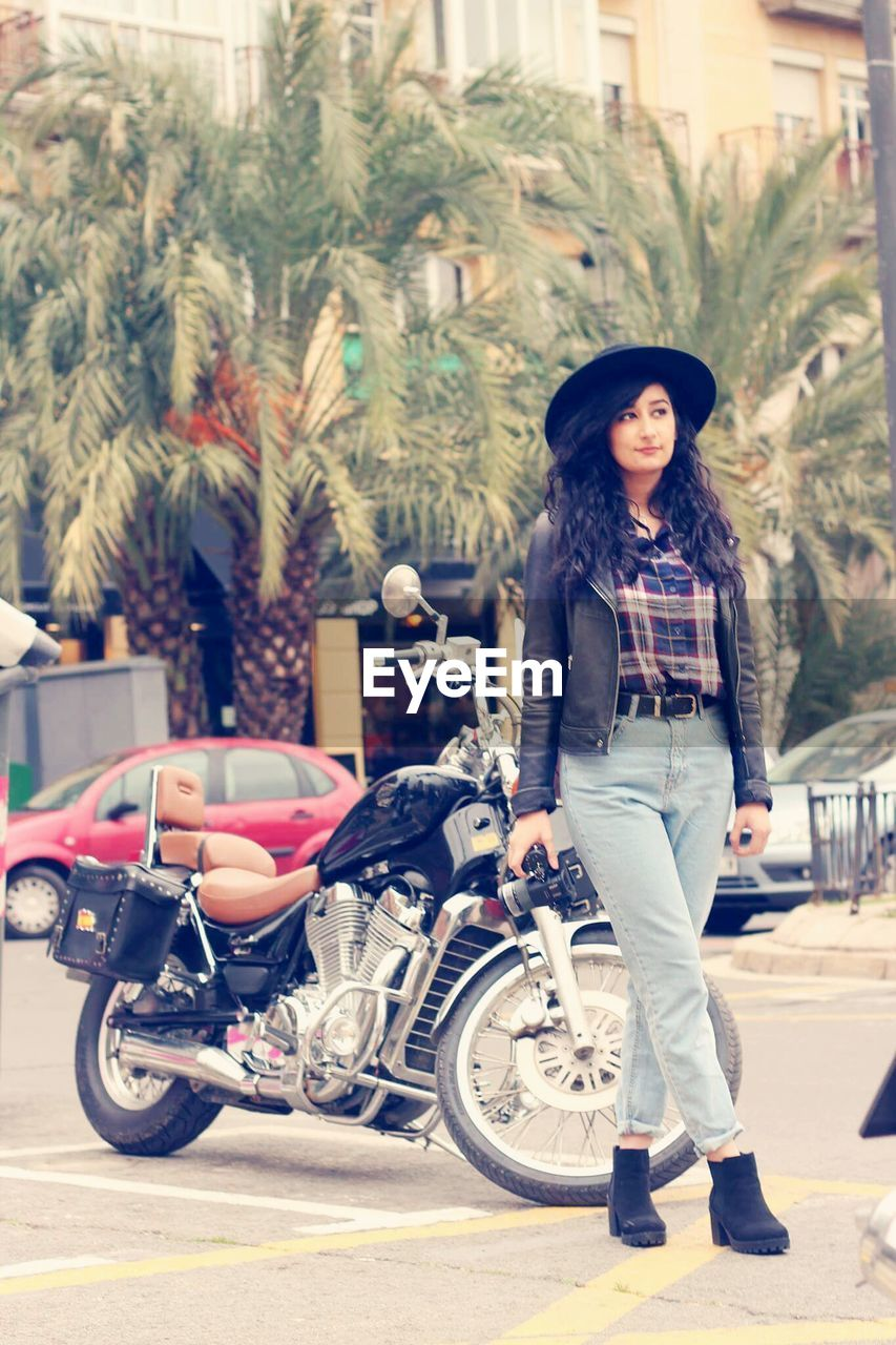 Full length of young woman with camera standing by parked motorcycle on street