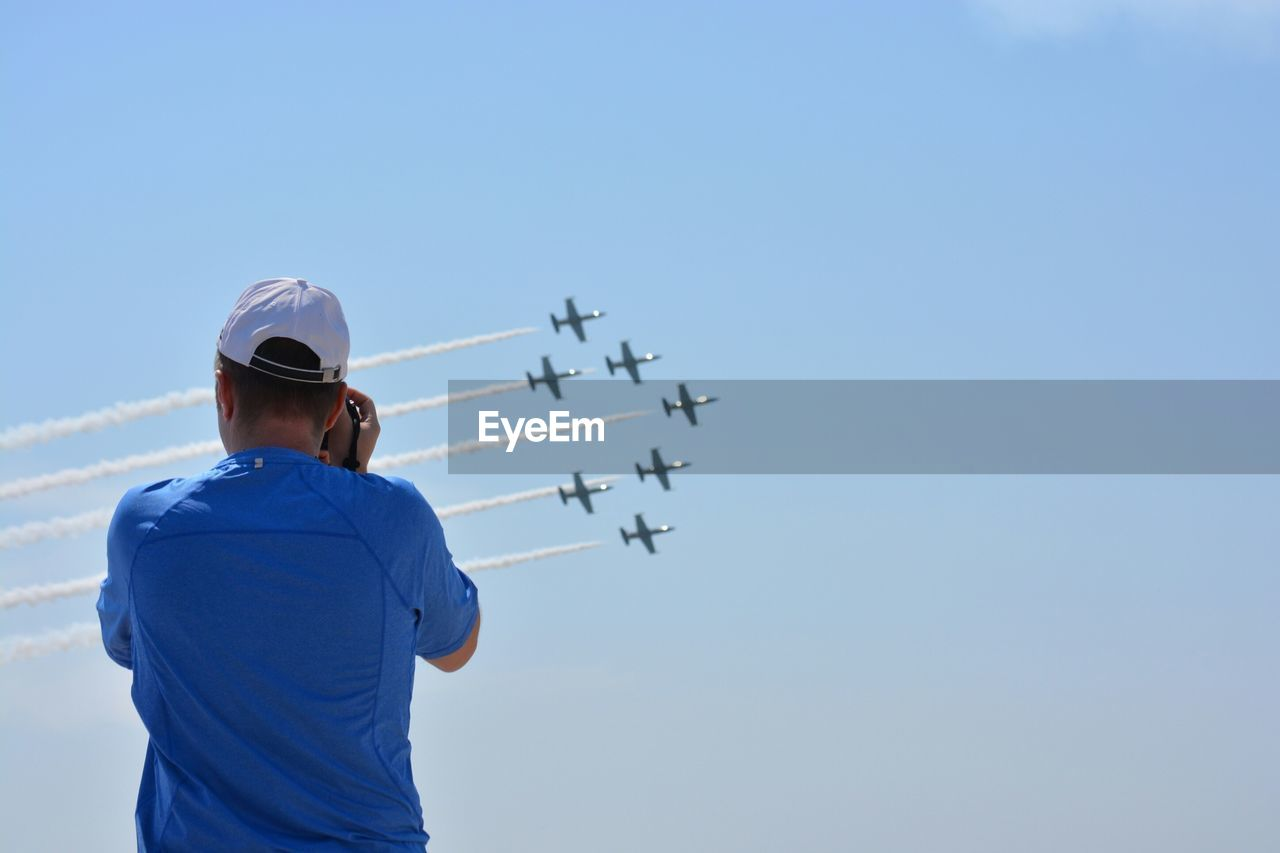 Rear View Of Man Photographing Air Show