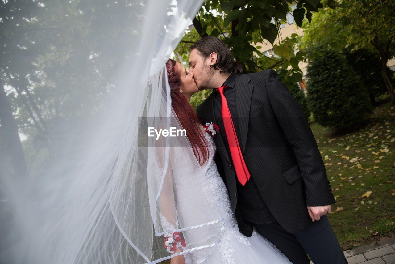 Tilt shot of young wedding couple kissing at back yard