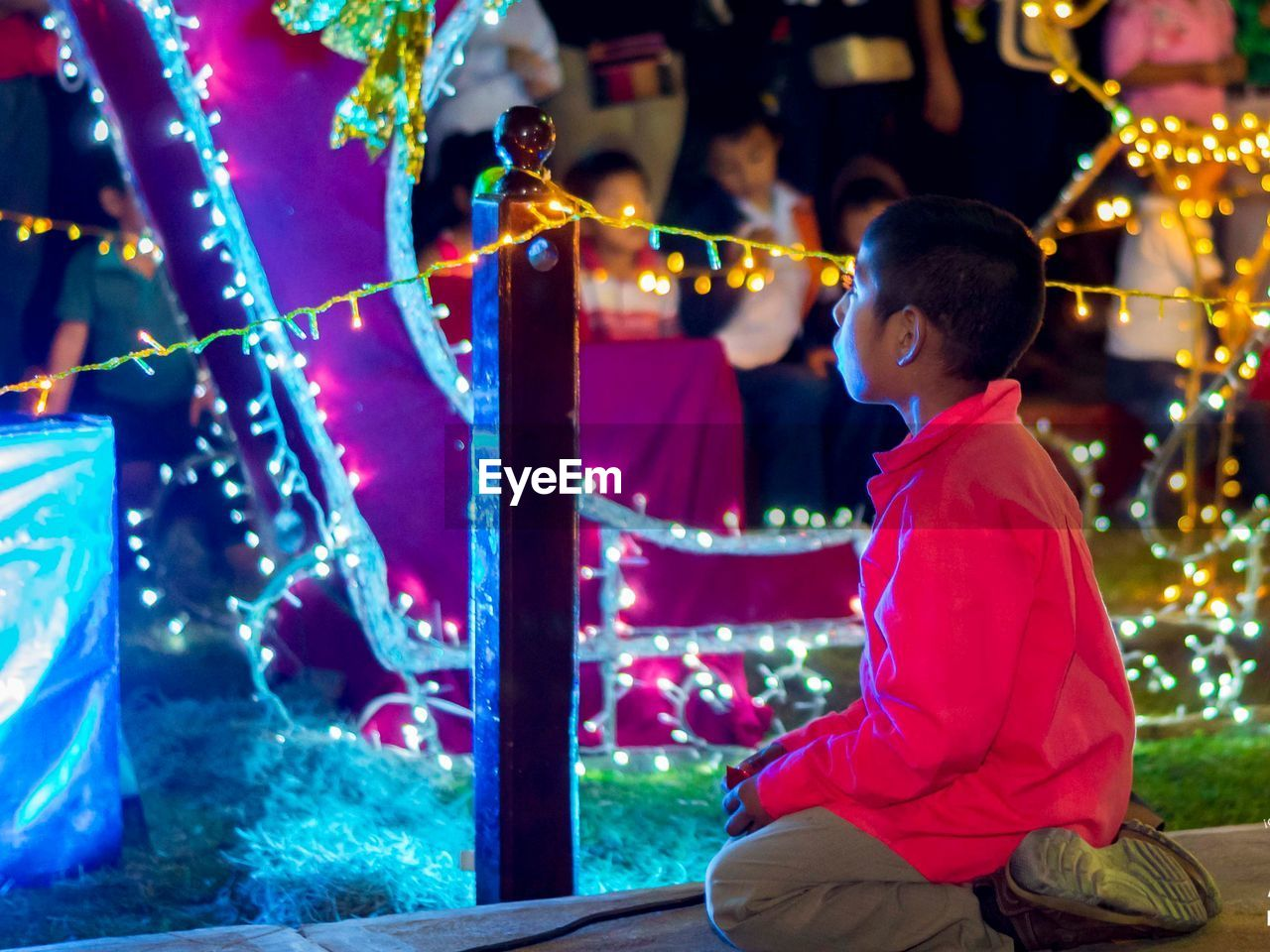 decoration, night, real people, illuminated, three quarter length, one person, lifestyles, sitting, lighting equipment, leisure activity, focus on foreground, celebration, side view, casual clothing, christmas, men, electric light, christmas decoration, adult, light