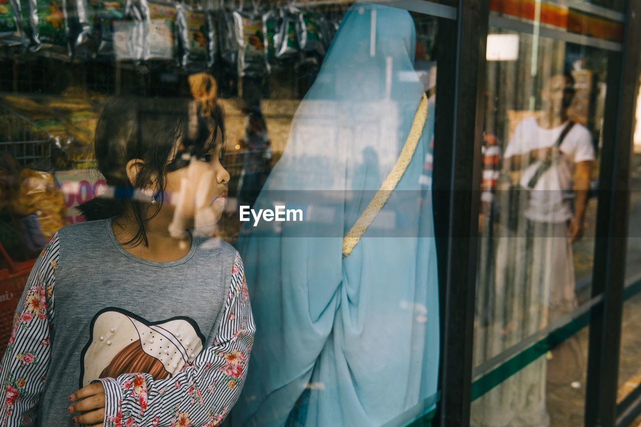 Girl Looking Through Window In Store
