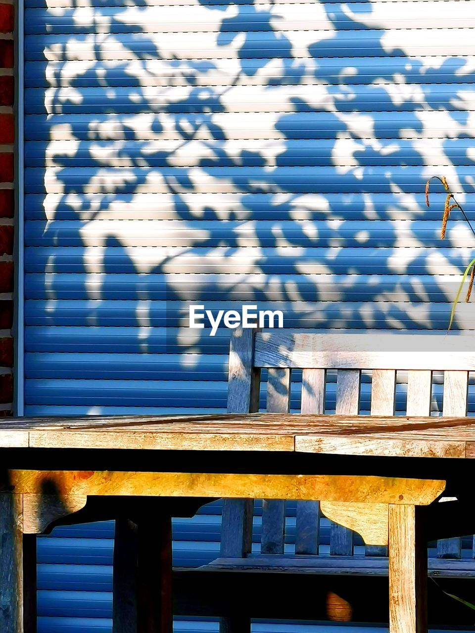 sunlight, shadow, railing, day, nature, wood - material, outdoors, no people, blue, built structure, table, architecture, pattern, water, seat, high angle view, metal, security, safety