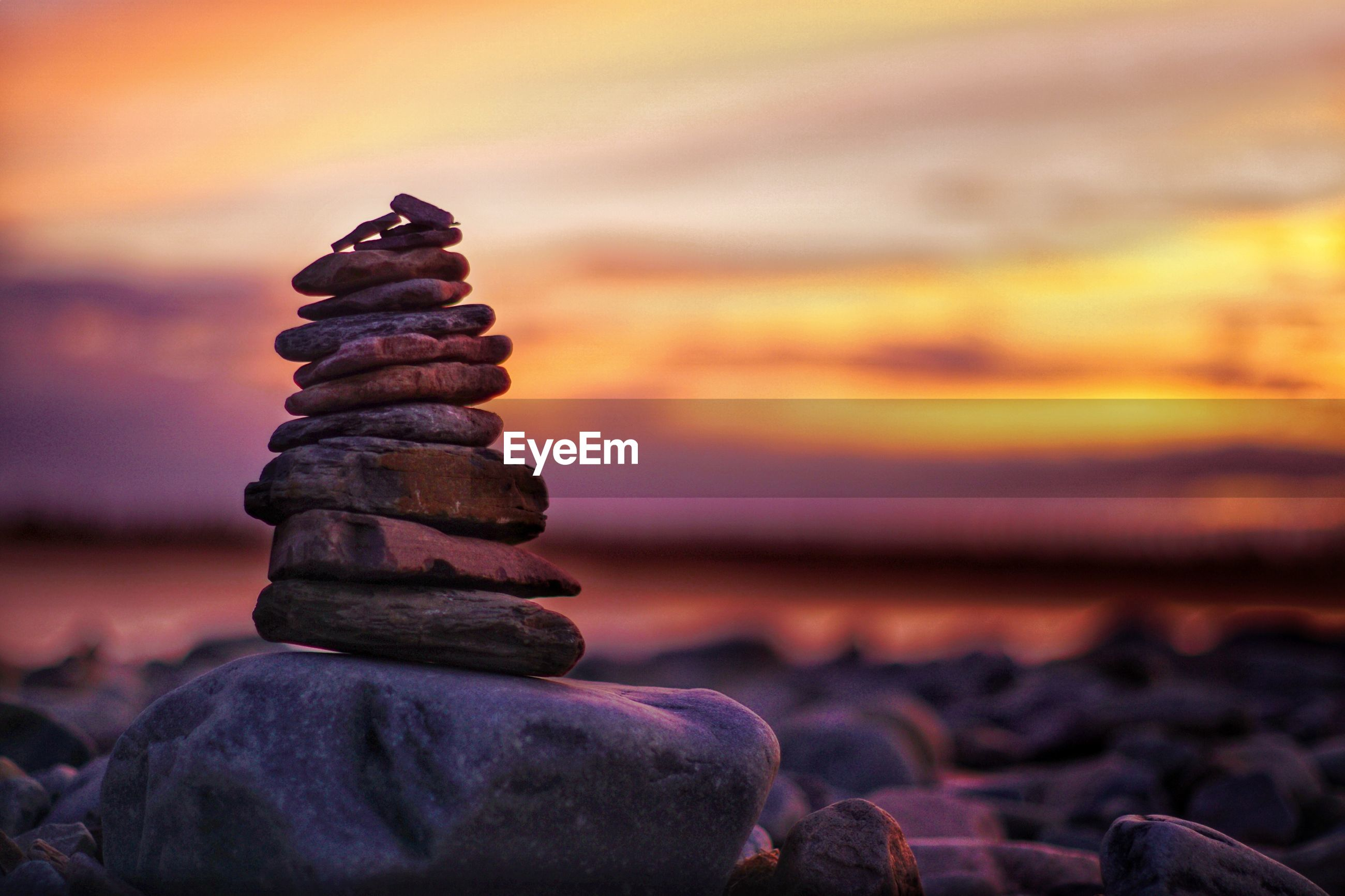Stack of stones at beach against sea and sky during sunset