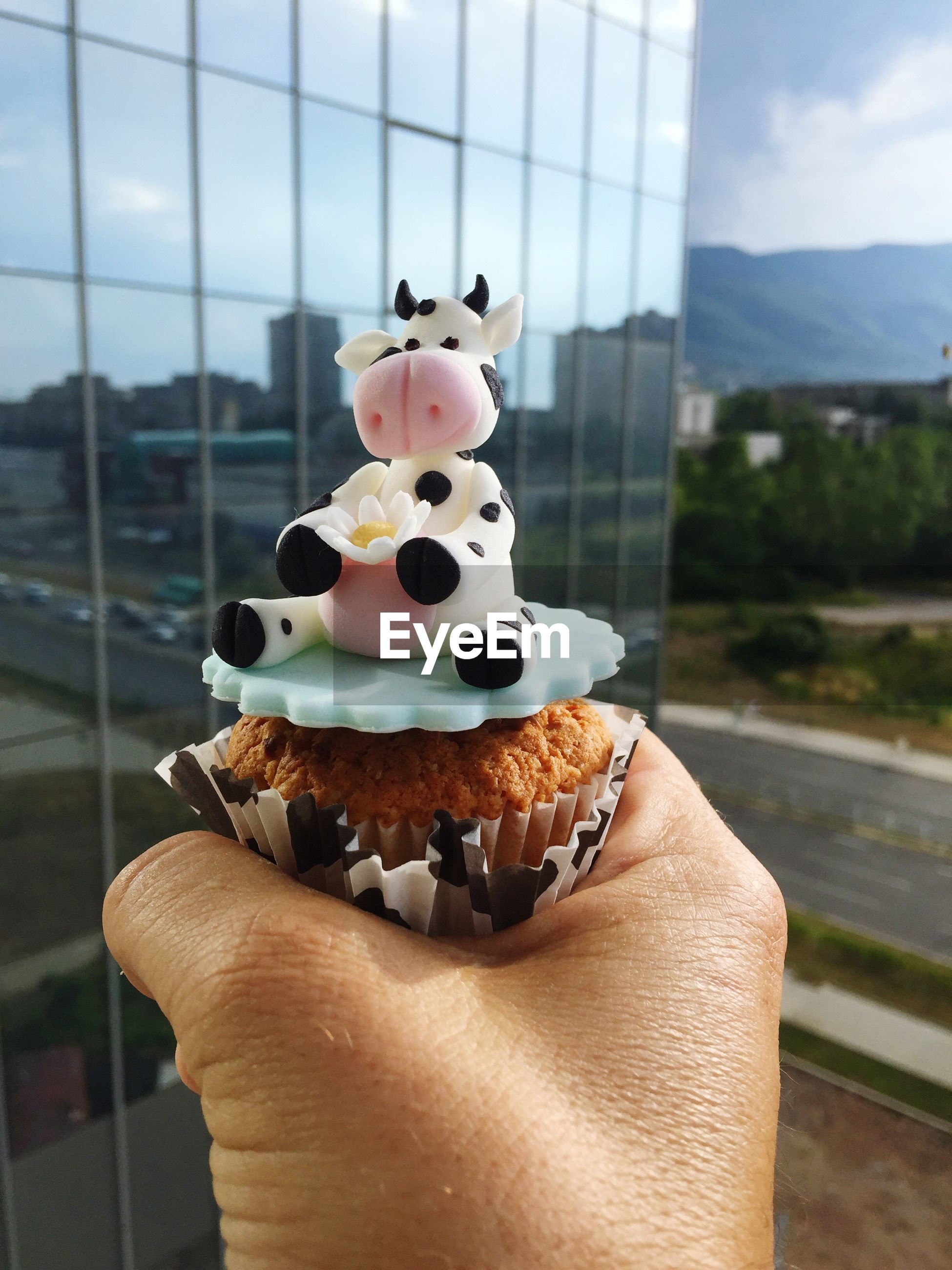 Cropped hand with cow figurine on cupcake against modern building