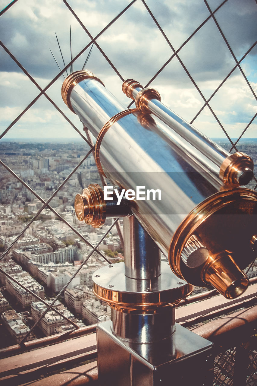Close-up of coin-operated binoculars overlooking cityscape