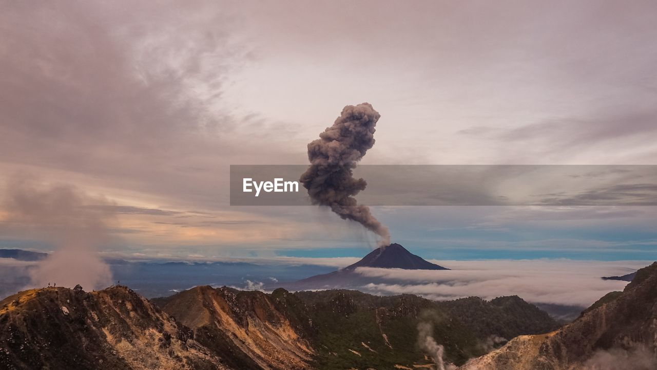 Smoke Emitting From Mountain Against Cloudy Sky