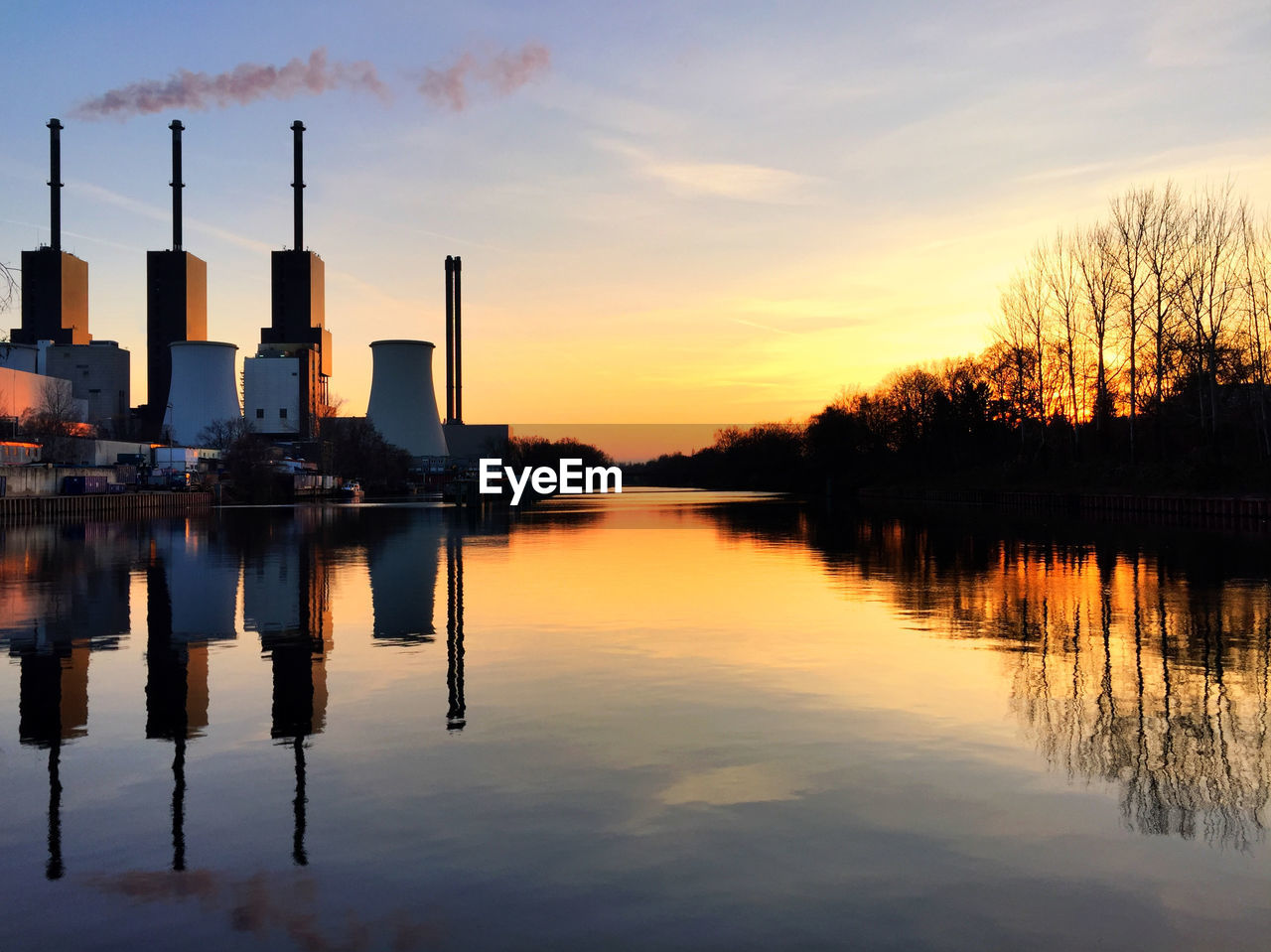 Smoke Stack Emitting Pollution From Power Plant With Reflection During Sunset