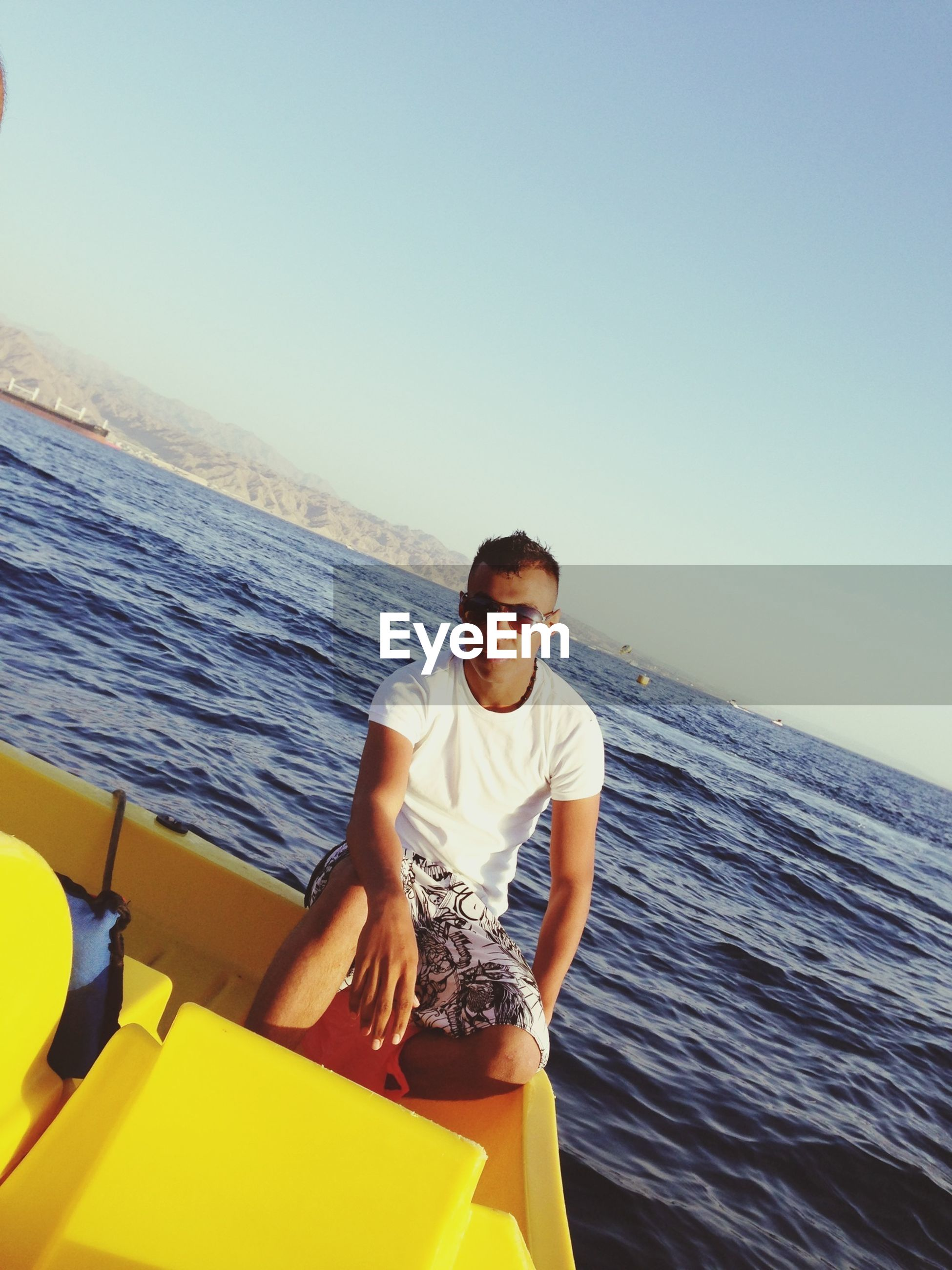 sea, water, clear sky, horizon over water, lifestyles, leisure activity, copy space, person, young adult, casual clothing, vacations, beach, young men, front view, portrait, standing, nature, full length