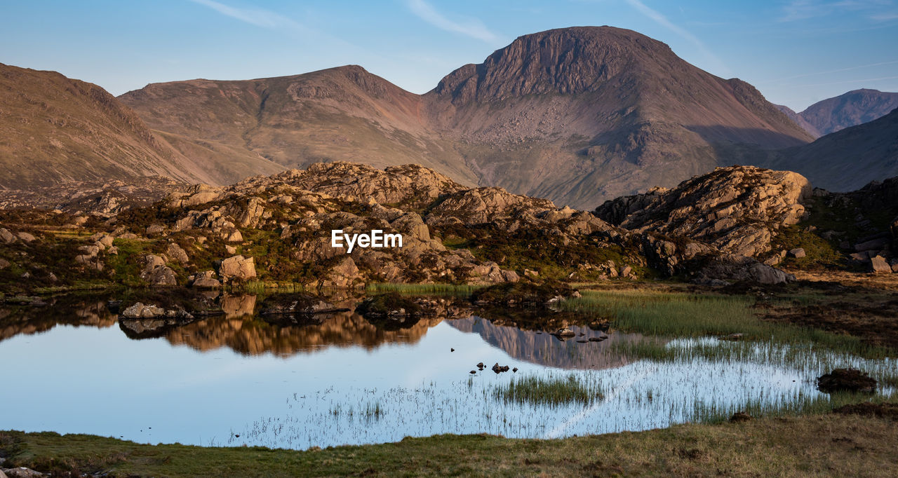 The evening light on the lakeland mountain of great gable reflecting in innominate tarn