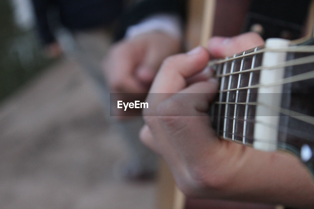 Close-Up Midsection Of Man Playing Guitar On Street