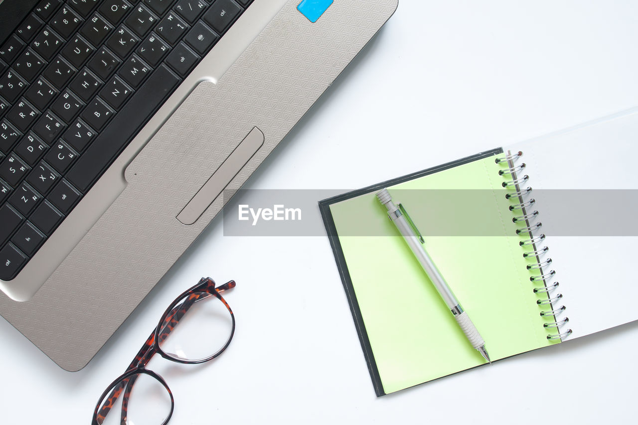 technology, connection, laptop, computer, wireless technology, table, eyeglasses, indoors, communication, high angle view, still life, glasses, book, publication, pen, computer equipment, no people, keyboard, portable information device, directly above, note pad