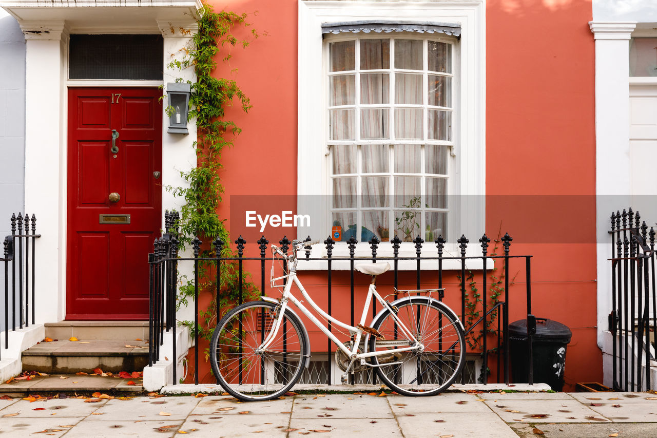 bicycle, architecture, building exterior, built structure, land vehicle, building, window, mode of transportation, transportation, red, no people, house, day, stationary, city, door, residential district, outdoors, railing, entrance, row house