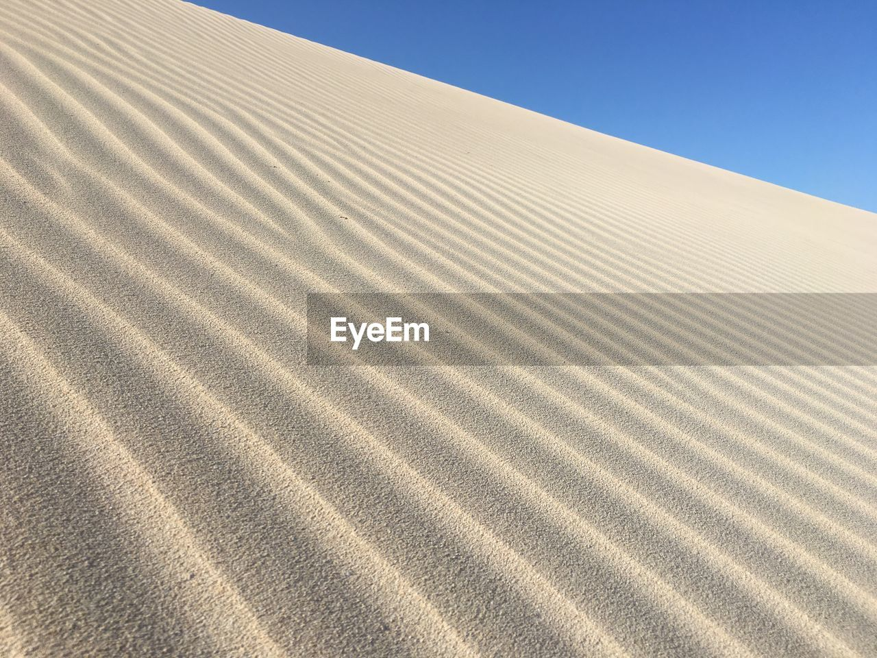 sand dune, sand, desert, land, sky, landscape, climate, arid climate, pattern, nature, scenics - nature, clear sky, no people, day, tranquility, wave pattern, tranquil scene, sunlight, beauty in nature, blue, outdoors