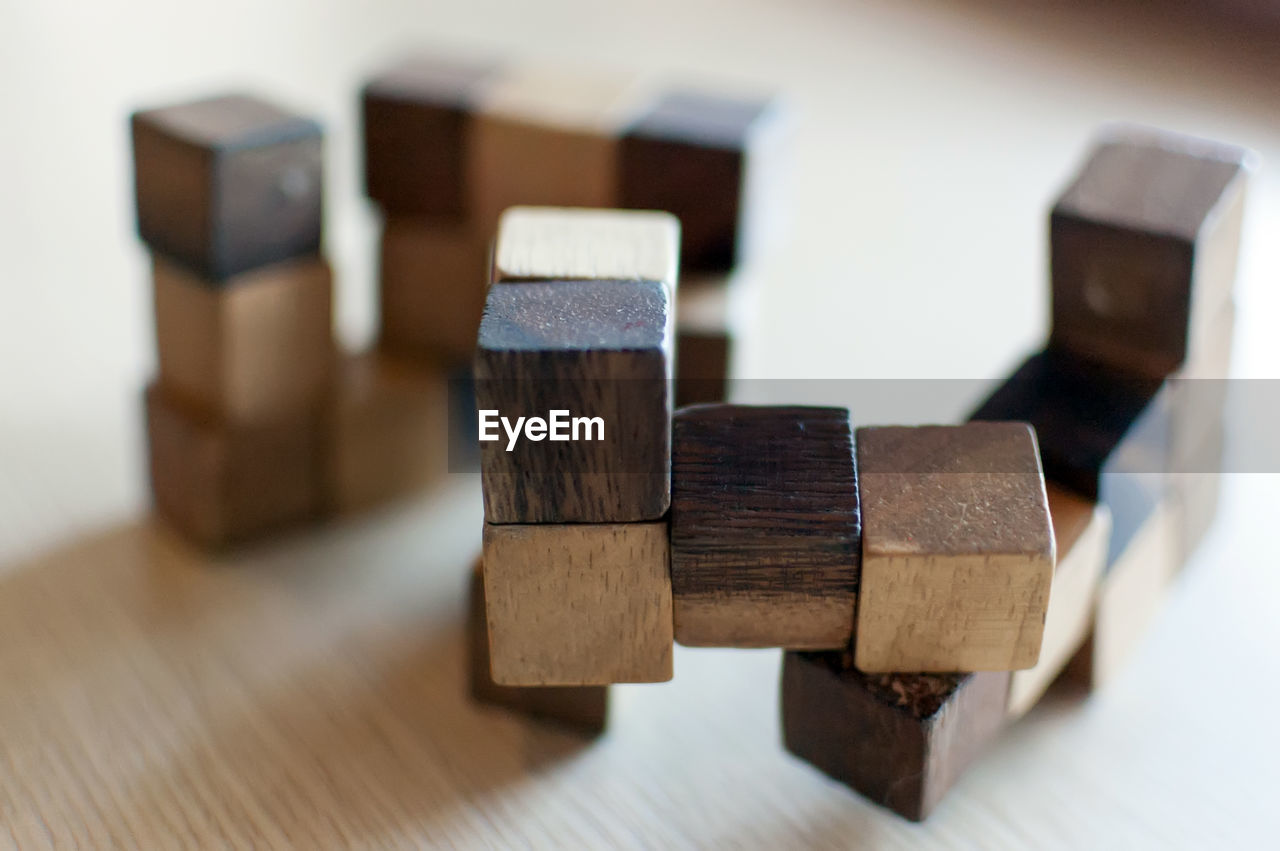 wood - material, still life, indoors, no people, close-up, toy, toy block, focus on foreground, selective focus, table, group of objects, large group of objects, brown, shape, stack, design, wood, pattern