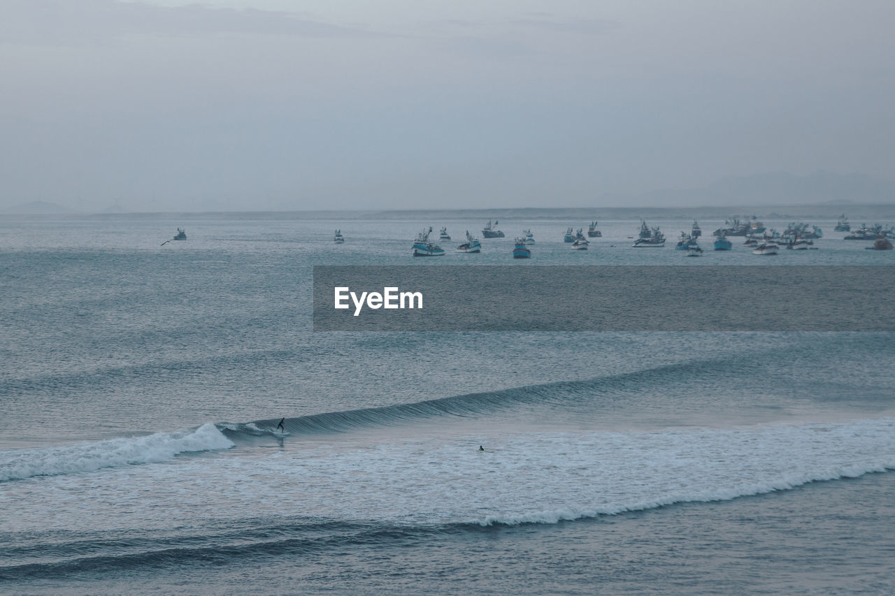 sea, water, sky, horizon, horizon over water, beach, land, scenics - nature, beauty in nature, nature, wave, motion, aquatic sport, sport, day, waterfront, surfing, group of people, tranquil scene, outdoors