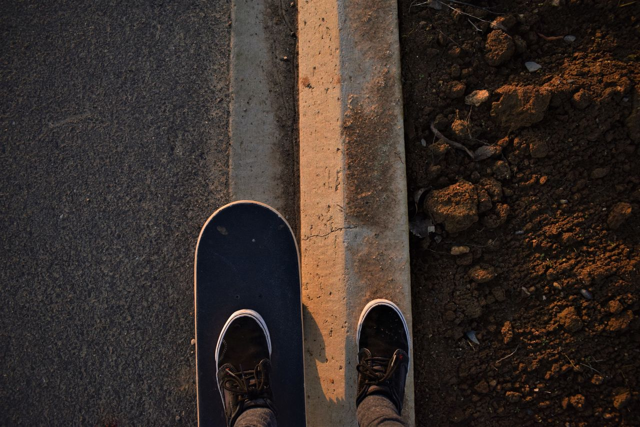 Low Section Of Person On Skateboard On Road