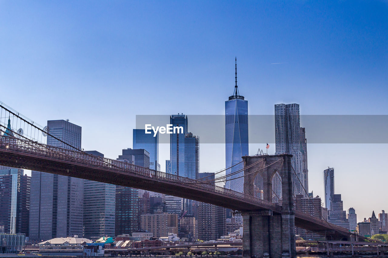 architecture, built structure, building exterior, sky, office building exterior, skyscraper, city, building, tall - high, tower, office, urban skyline, modern, travel destinations, cityscape, landscape, nature, clear sky, travel, day, no people, outdoors, financial district, bridge - man made structure, spire