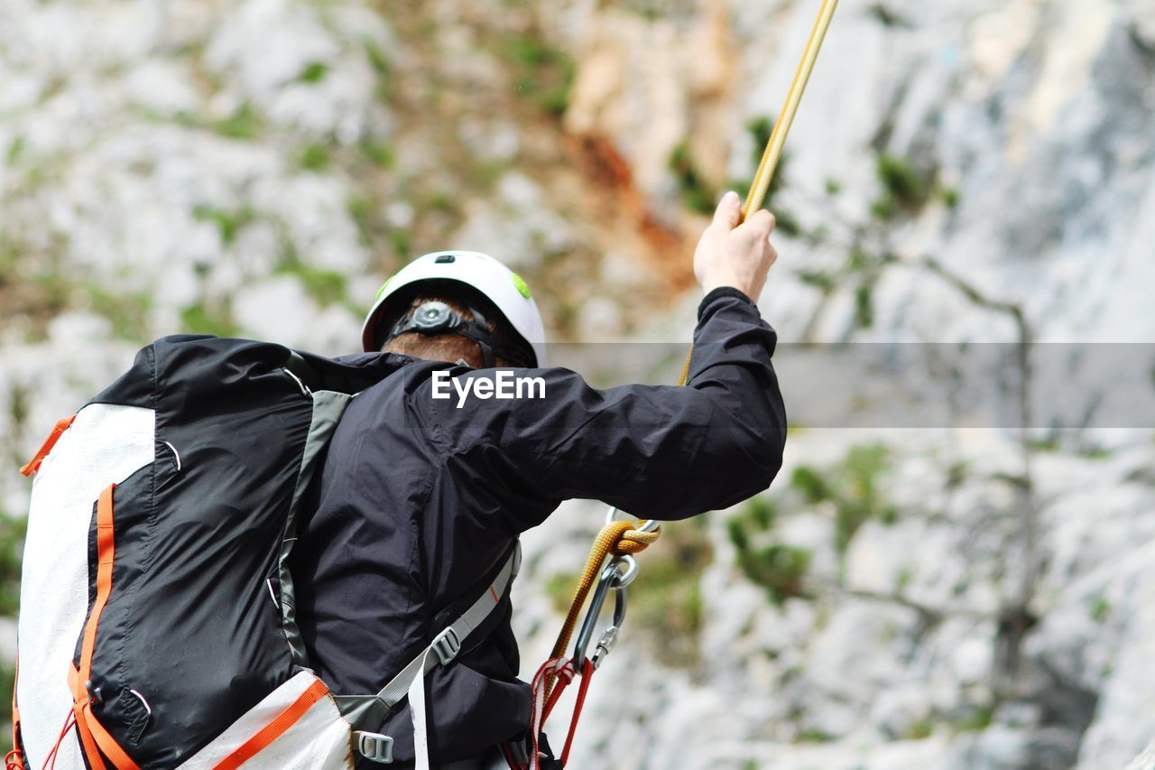 Man With Backpack Rappelling On Mountain