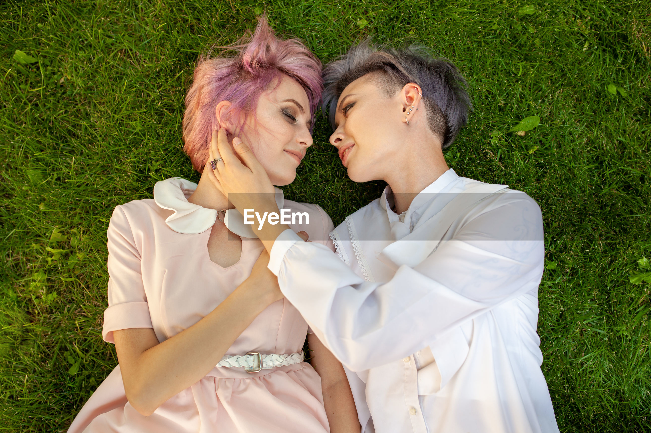 Directly above shot of romantic lesbians lying on grassy field