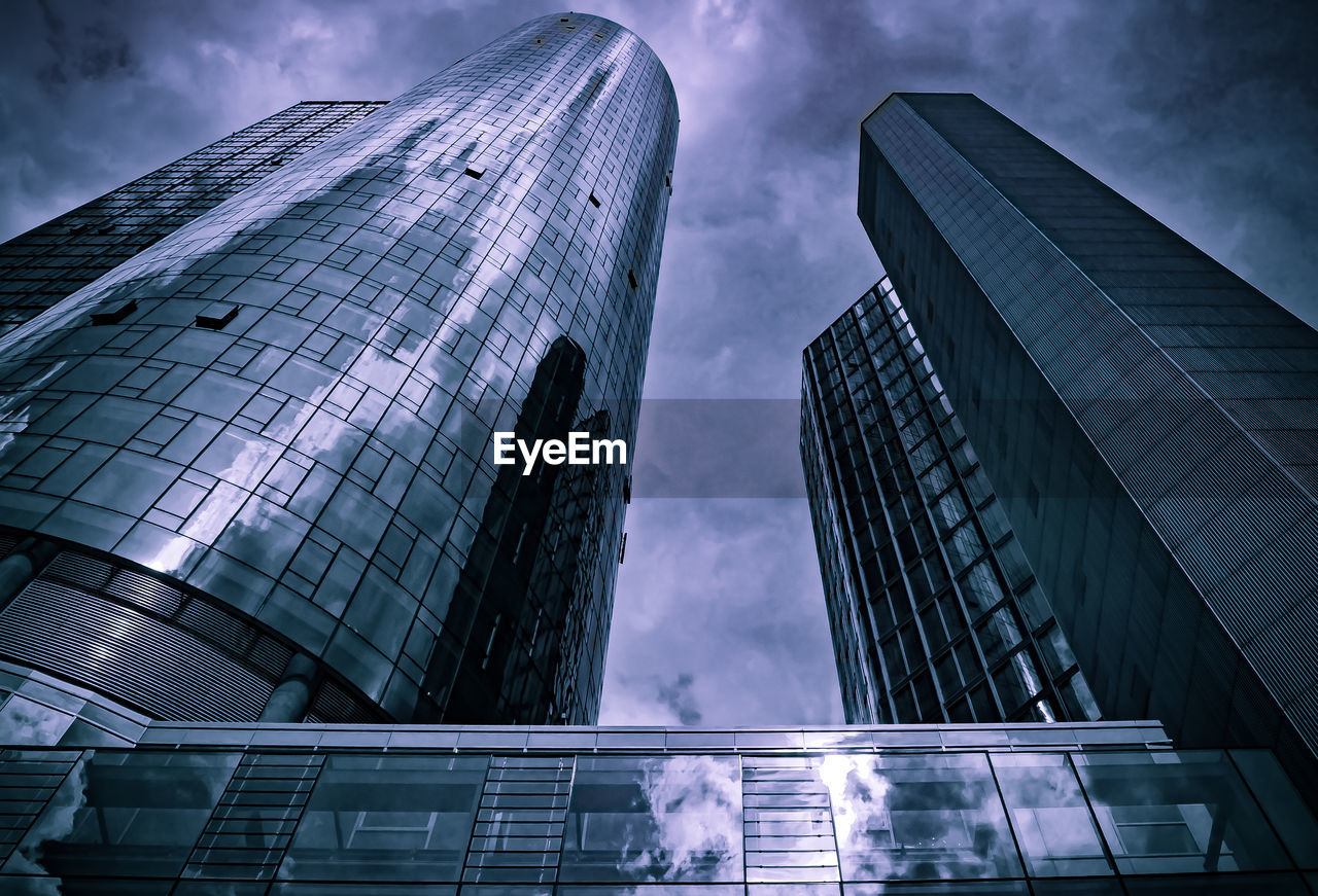 Low angle view of modern buildings against cloudy sky in city