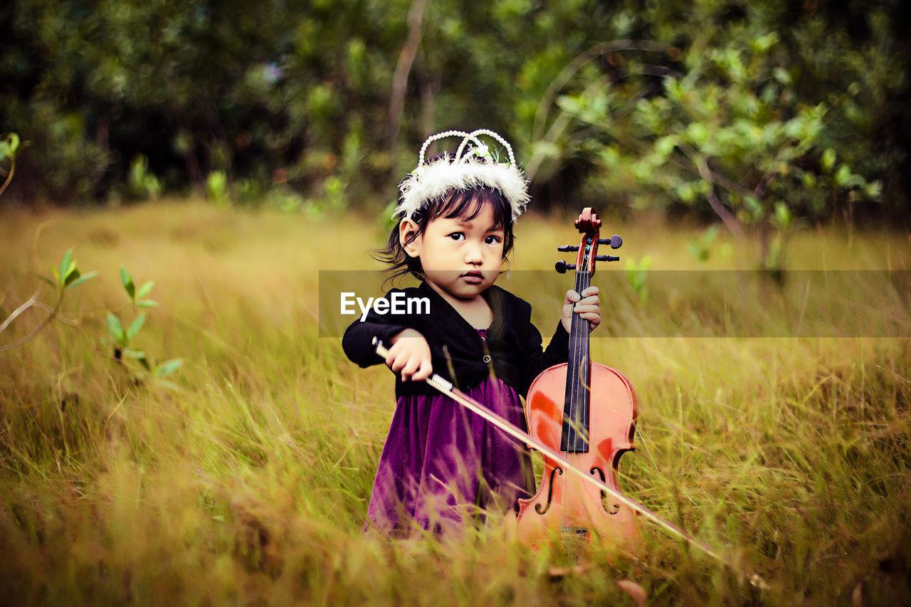 Girl Playing Violin On Grassland