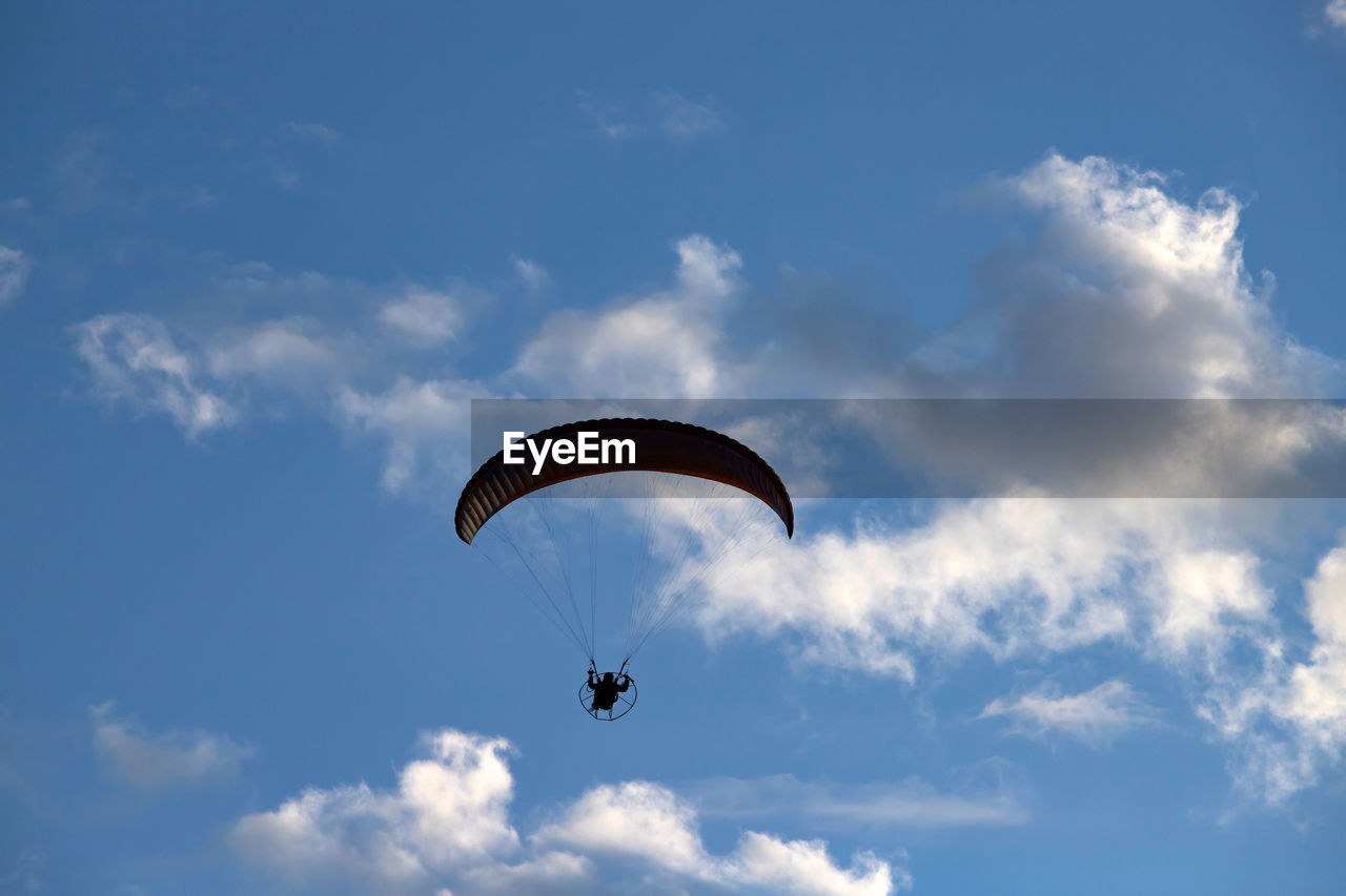 extreme sports, mid-air, sky, adventure, cloud - sky, parachute, flying, sport, paragliding, low angle view, unrecognizable person, leisure activity, real people, one person, joy, transportation, day, lifestyles, exhilaration, freedom, outdoors