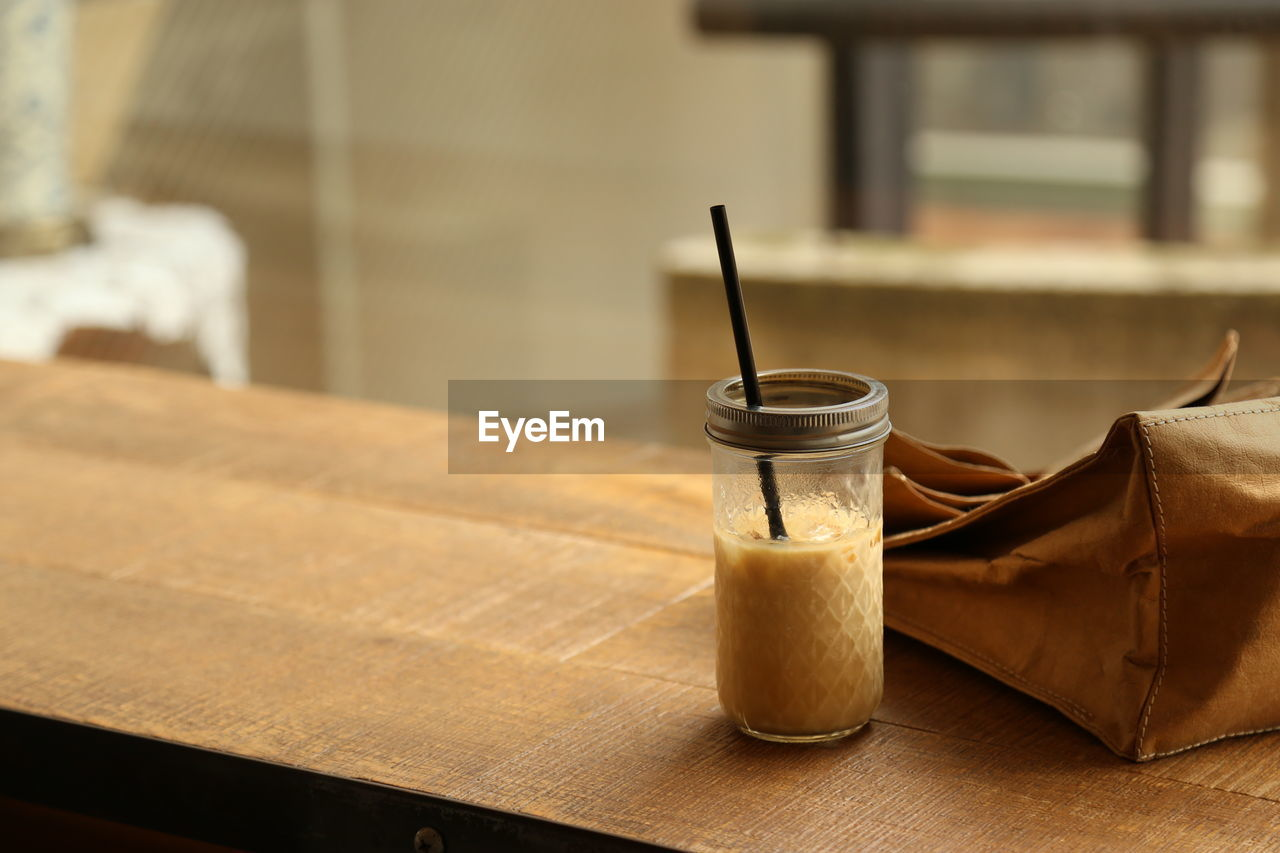Close-up of drink by purse on table
