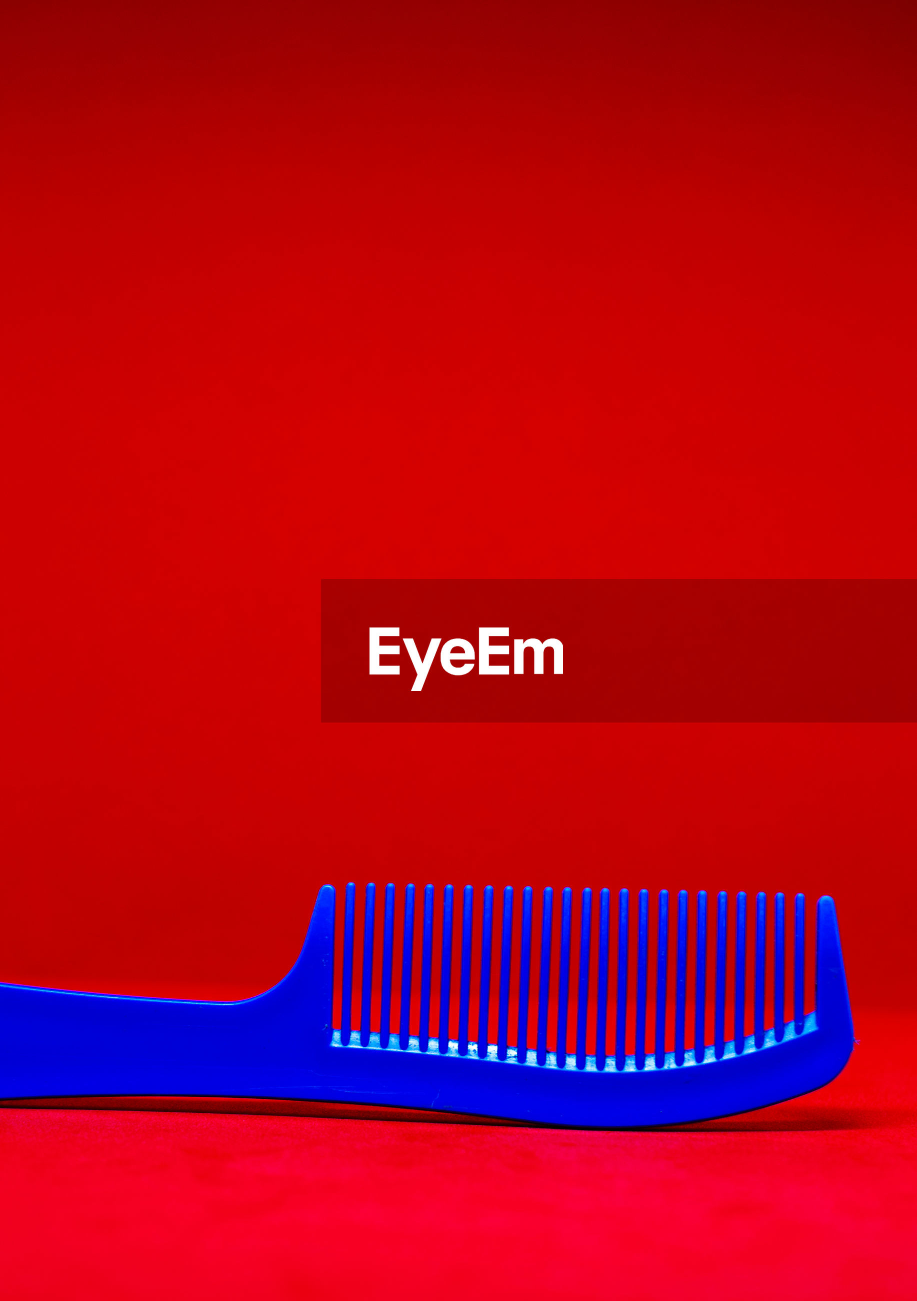 Close-up of blue comb against red background