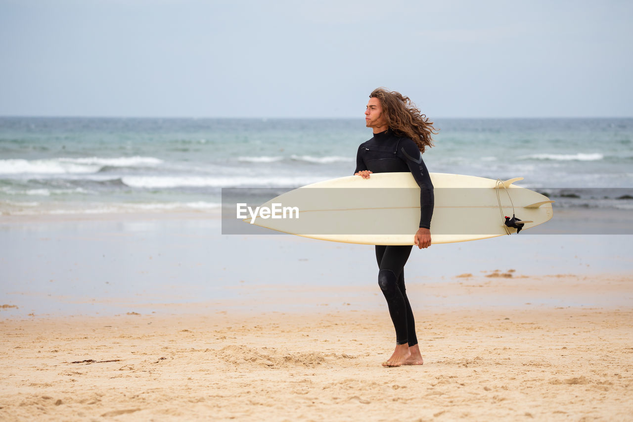 Man standing with surfboard at beach