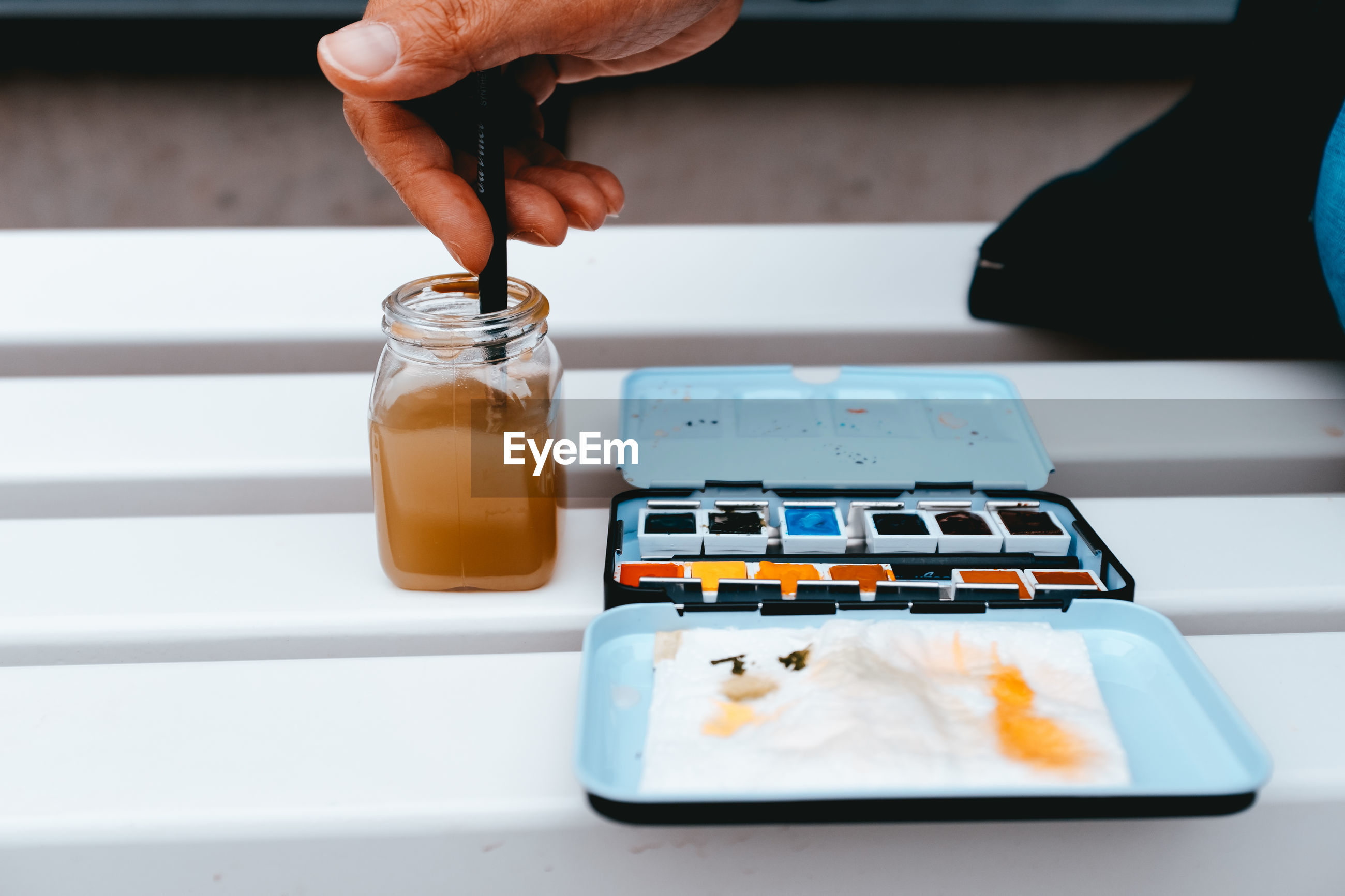 Cropped image of person with painting equipment on table