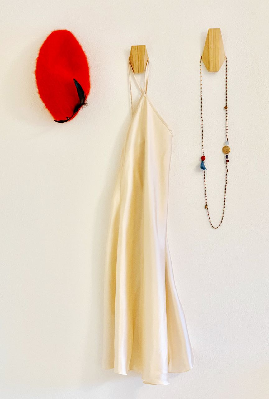 indoors, no people, still life, white background, hanging, red, wall - building feature, white color, studio shot, clothing, close-up, textile, copy space, decoration, jewelry, high angle view, fashion, art and craft, table, representation
