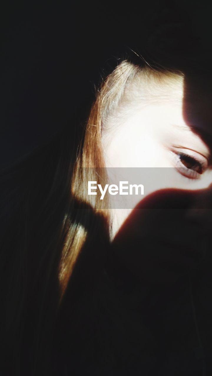 Sunlight falling on woman face in darkroom