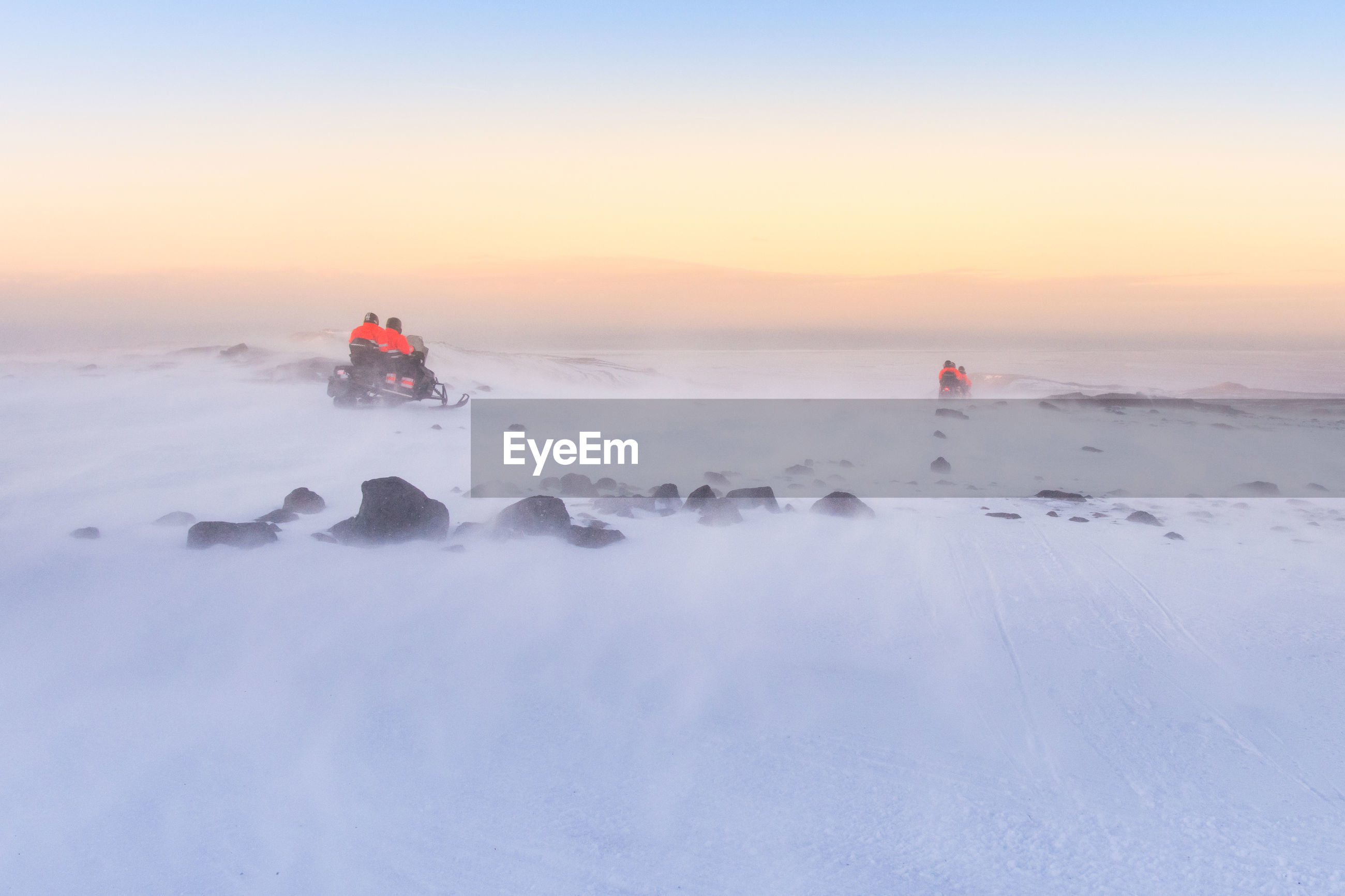 People on snow covered land against sky during sunset