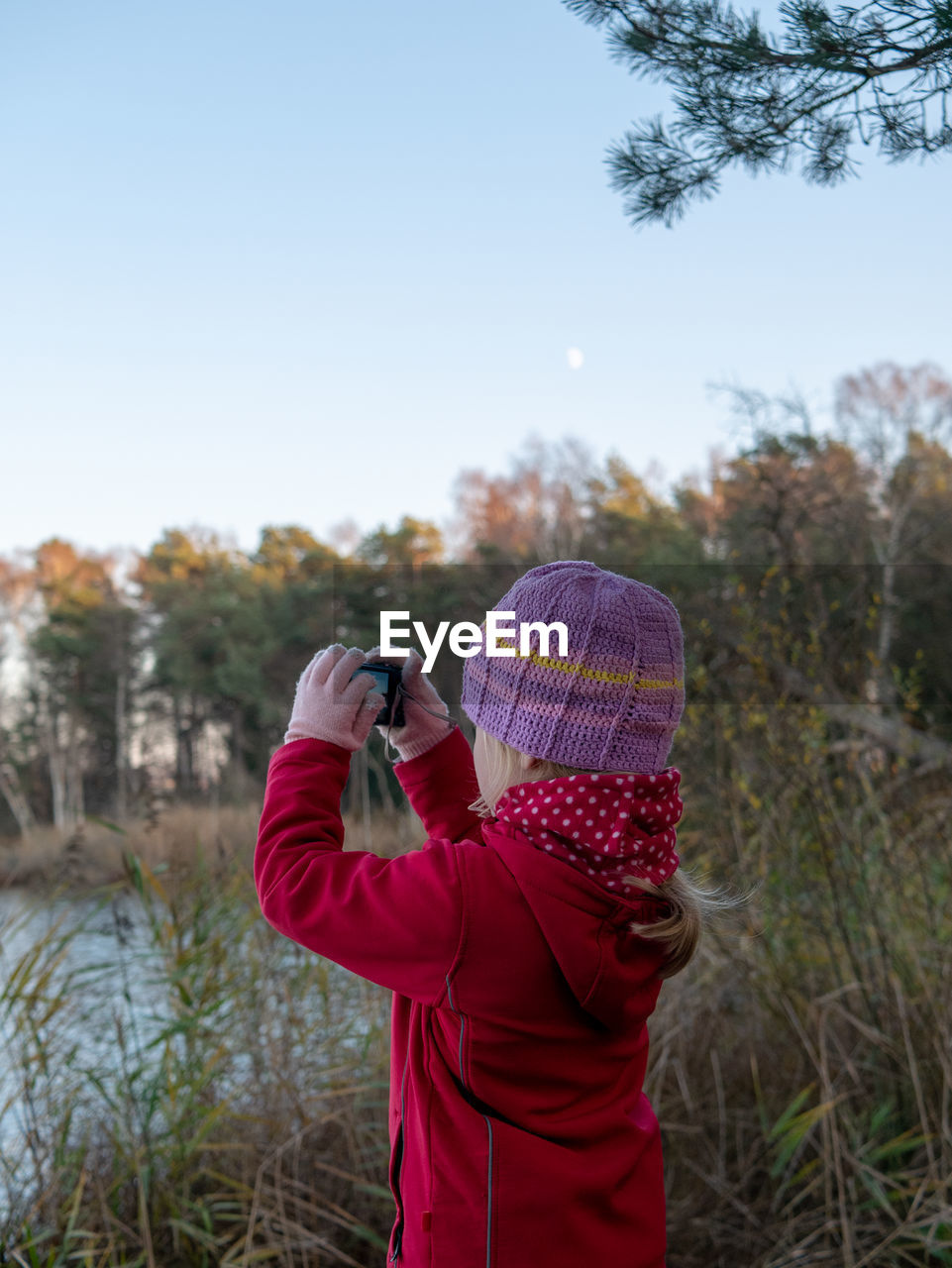 photography themes, photographing, one person, technology, holding, activity, real people, sky, rear view, lifestyles, leisure activity, mobile phone, wireless technology, nature, standing, plant, waist up, women, adult, outdoors, warm clothing, photographer