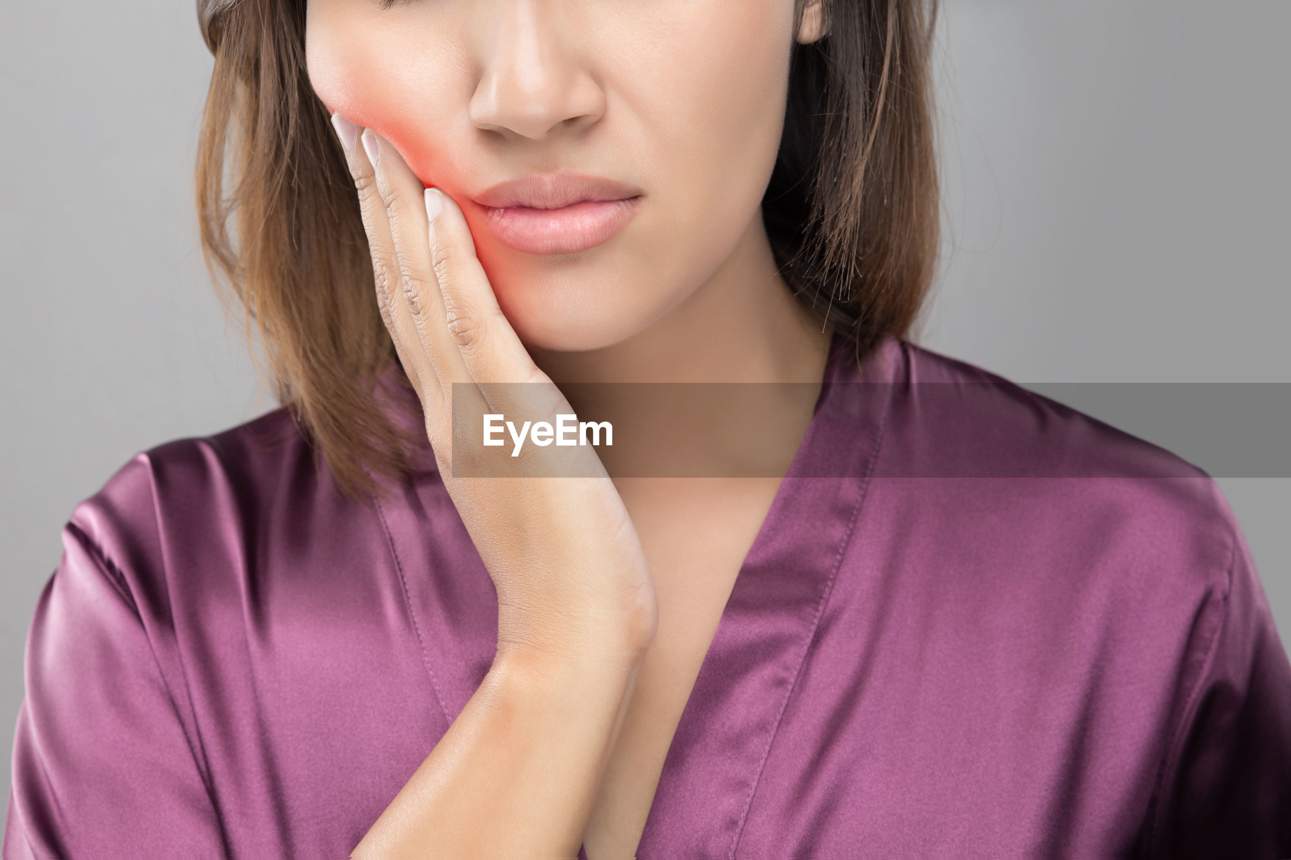 Close-up of woman suffering from toothache against gray background