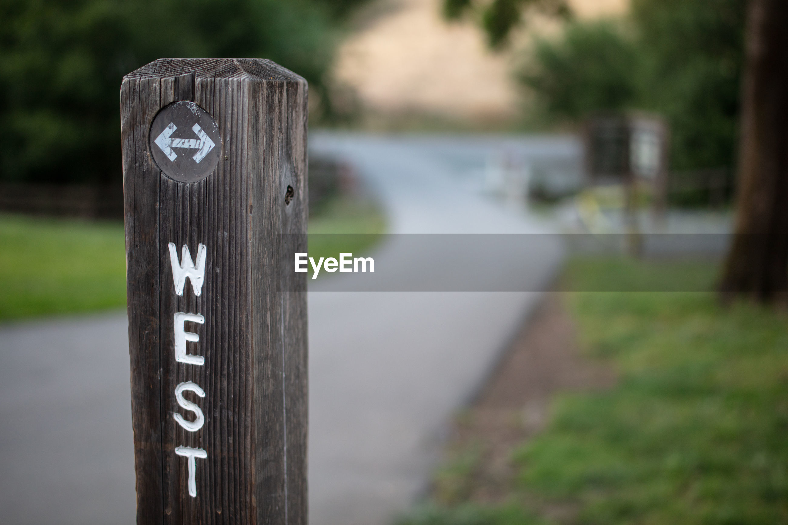CLOSE-UP OF INFORMATION SIGN ON WOODEN POST AT FIELD