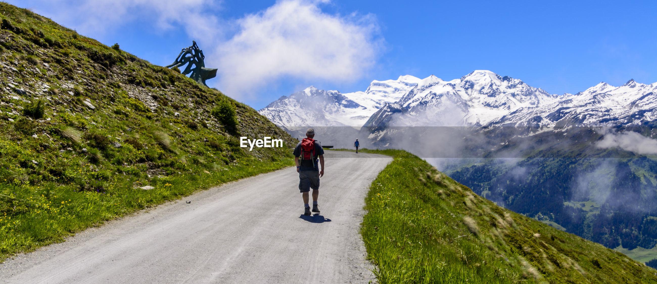 Full length of man on road in mountain landscape against sky