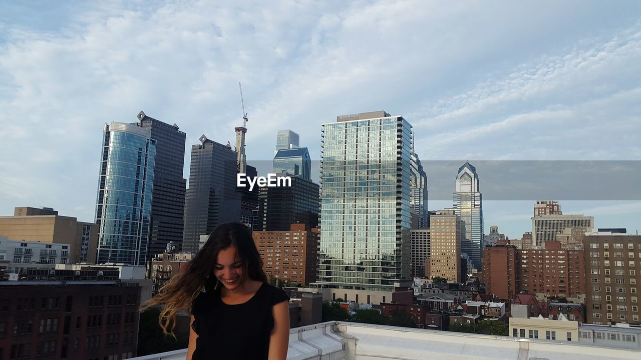 Young Woman Laughing Against Modern Buildings In City