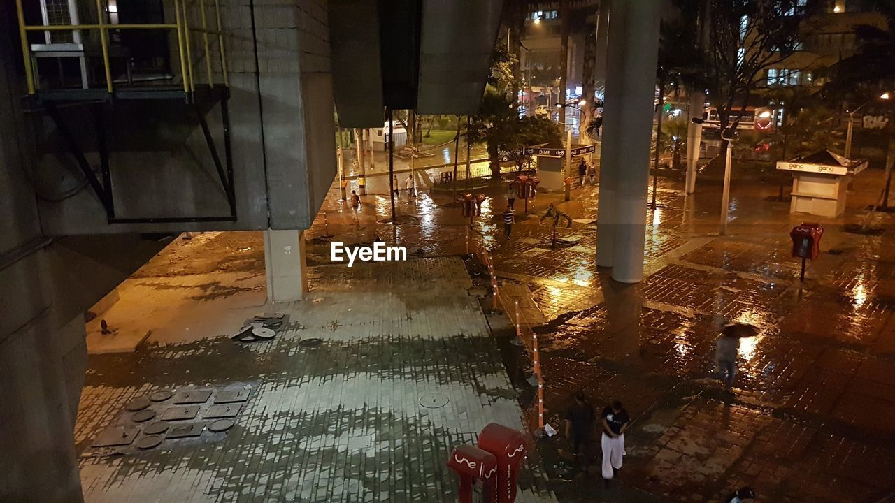 architecture, city, building exterior, water, built structure, street, wet, illuminated, night, incidental people, building, puddle, reflection, rain, nature, high angle view, real people, outdoors, rainy season