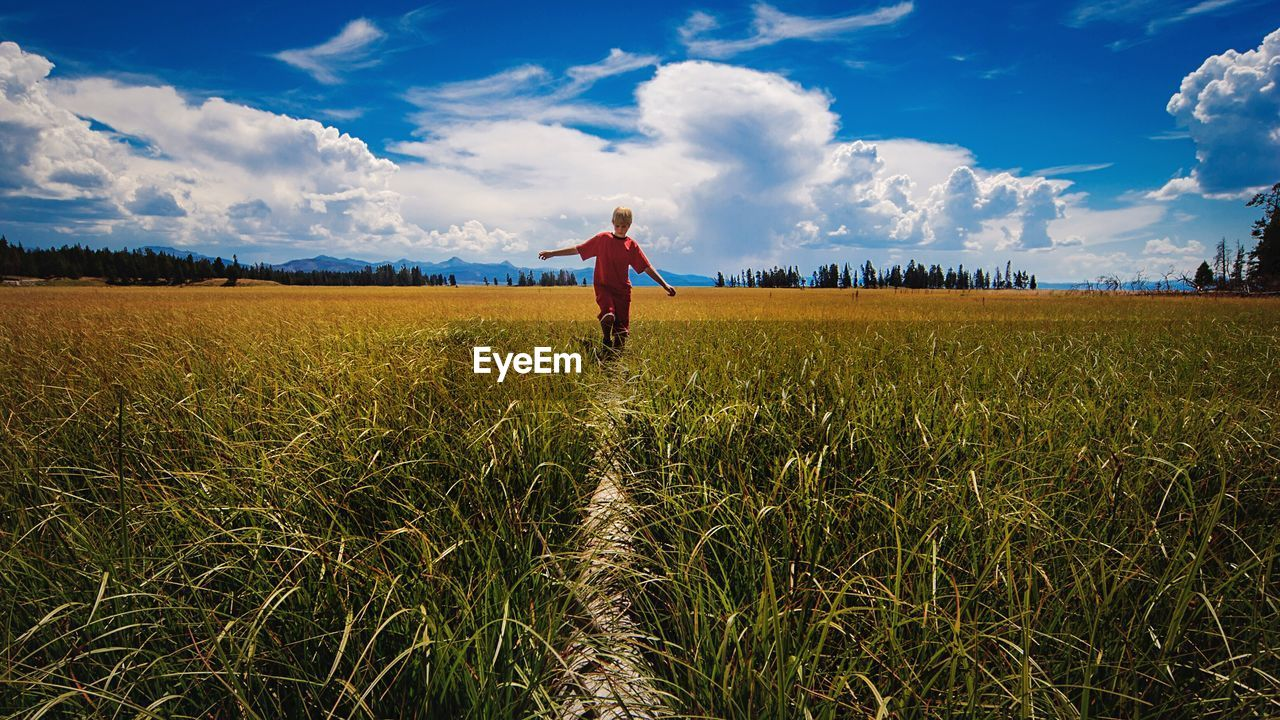 Young Man Walking On Grassy Field Against Cloudy Sky During Sunny Day