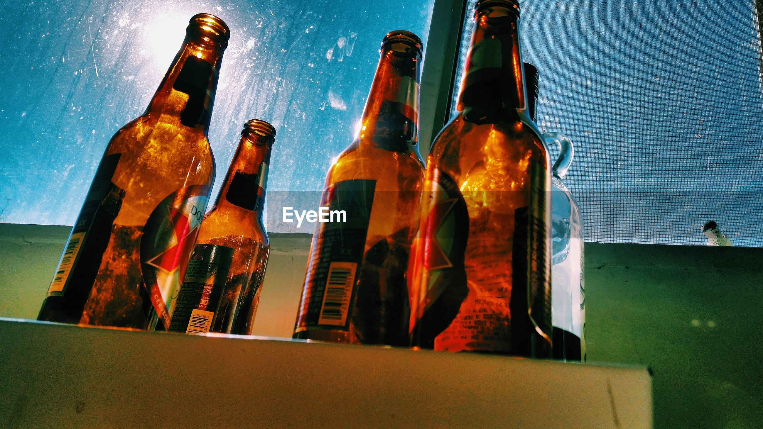 LOW ANGLE VIEW OF BEER BOTTLES ON GLASS