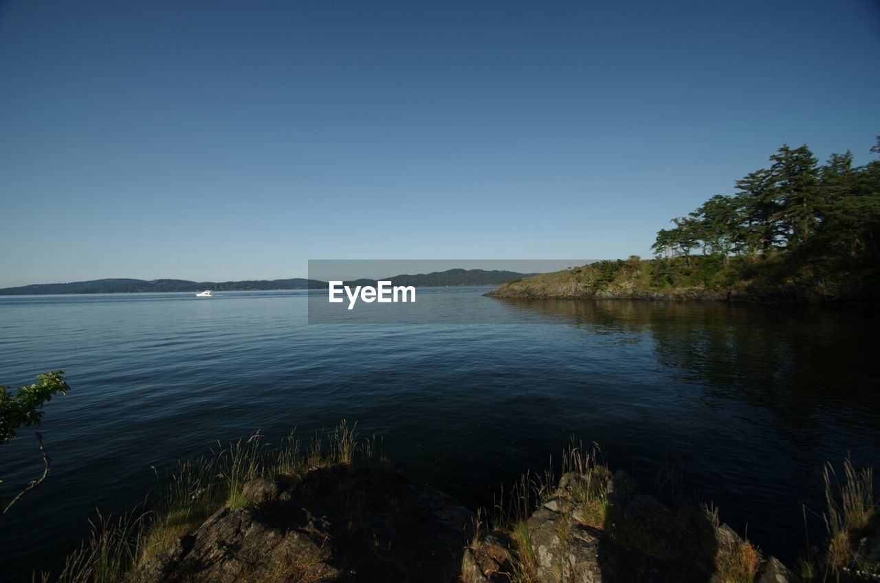 Idyllic view of lake against clear sky