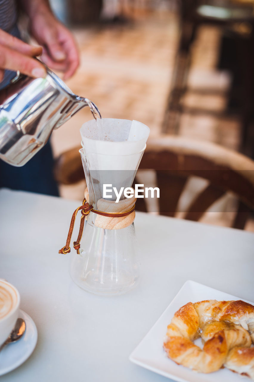 food and drink, drink, refreshment, hand, human hand, food, pouring, indoors, one person, coffee, coffee - drink, focus on foreground, table, holding, freshness, real people, human body part, cafe, preparation, glass, coffee shop