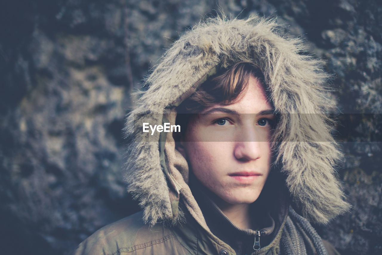 Close-Up Portrait Of Teenage Boy In Warm Clothing Standing Outdoors